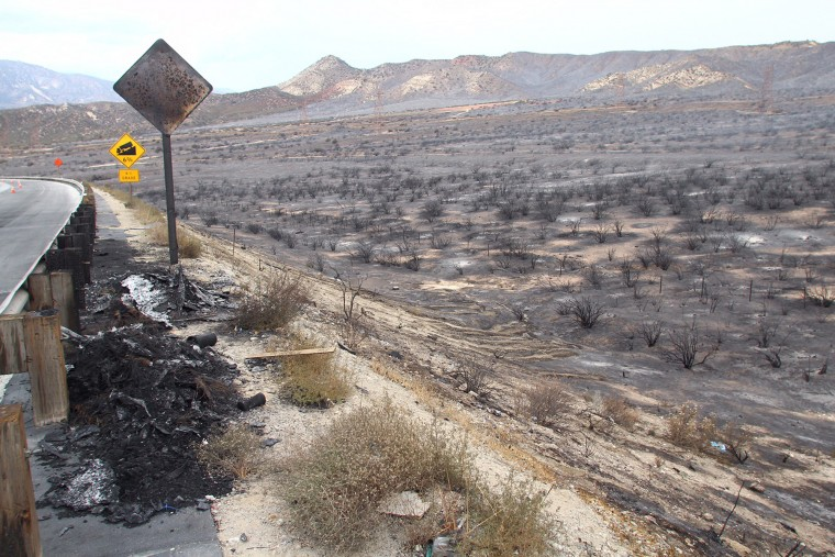 Burned terrain is seen on the reopened southbound side of Interstate 15, the main connector between Southern California and Las Vegas in the Cajon Pass, Calif., on Saturday, July 18, 2015. The fire swept across Interstate 15 on Friday, destroying the vehicles before burning three homes and 44 more vehicles in the community of Baldy Mesa. It has blackened 5.5 square miles. (Matt Hartman/Associated Press)