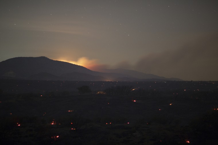 A new fire, being dubbed the Pine Fire, is seen in the distance as a landscape of embers burns in the wake of the North Fire, which caused people to abandon their vehicles and flee as flames jumped the 215 freeway in the early morning hours of July 18, 2015 near Victorville, California. The fire has burned across 3,500 acres and a private drone was reported to have raised serious safety concerns for aircraft pilots fighting the fire. (David McNew/Getty Images)