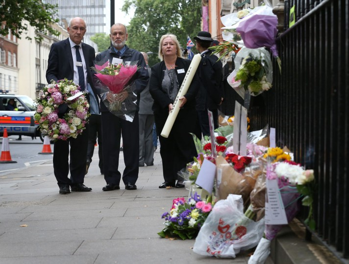 George Psaradakis (second from left), driver of the double decker bus that was targeted by bomber Hasib Hussain in 2005, stands with transport officials as he carries flowers during a remembrance ceremony near Tavistock Square on July 7, 2015 in London, England. Today is the 10th anniversary of the 7/7 bombings, when four suicide bombers struck transport system in central London on July 7, 2005, killing 52 people and injuring more than 770 in simultaneous attacks. (Photo by Peter Macdiarmid/Getty Images)