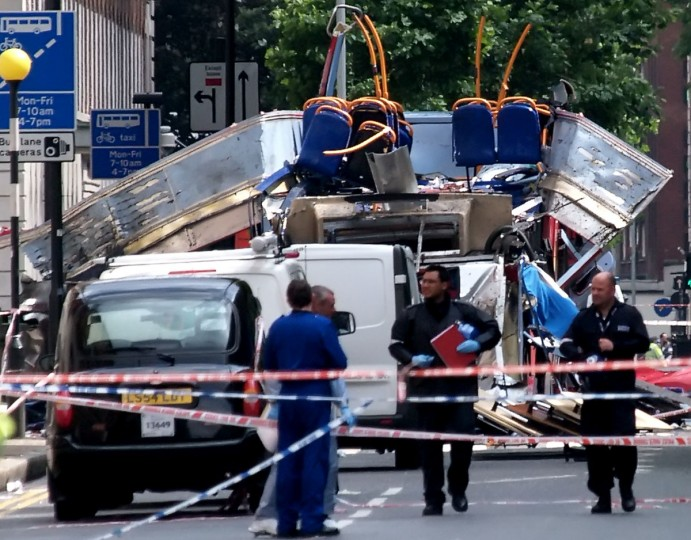 British police forensic experts walk away from the wreckage of a double-decker London bus which was ripped apart by an explosion in Russell Square in central London, Thursday July 7, 2005. (AP PHOTO/Max Nash)