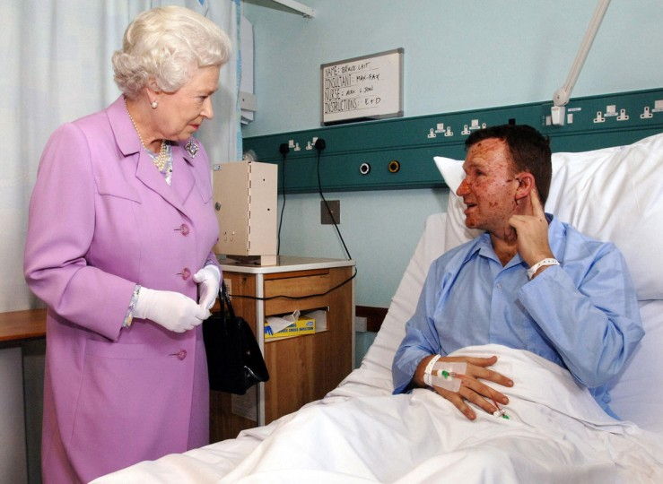 Britain's Queen Elizabeth II meets Bruce Lait, 32, a professional dancer from Ipswich at the Royal London Hospital in London's east end, on July 8, 2005. Lait was on the tube train travelling between Aldgate Station and Liverpool Street Station when a bomb exploded. He is explaining to the Queen how the hearing in his left ear was damaged by the blast. He was travelling to London to rehearse for a show he was scheduled to appear in with dance partner Crystal Main. (FIONA HANSON/AFP/Getty Images)