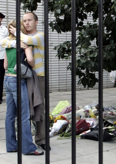 A couple hugs near flowers left in memory of the victims of the bomb attacks at King's Cross in London on July 9, 2005. In London's hushed streets, rapidly expanding floral shrines and anguished posters appealing for scraps of information about missing loved ones were a constant reminder of the bombing attacks. (PHILIPPE HUGUEN/AFP/Getty Images)