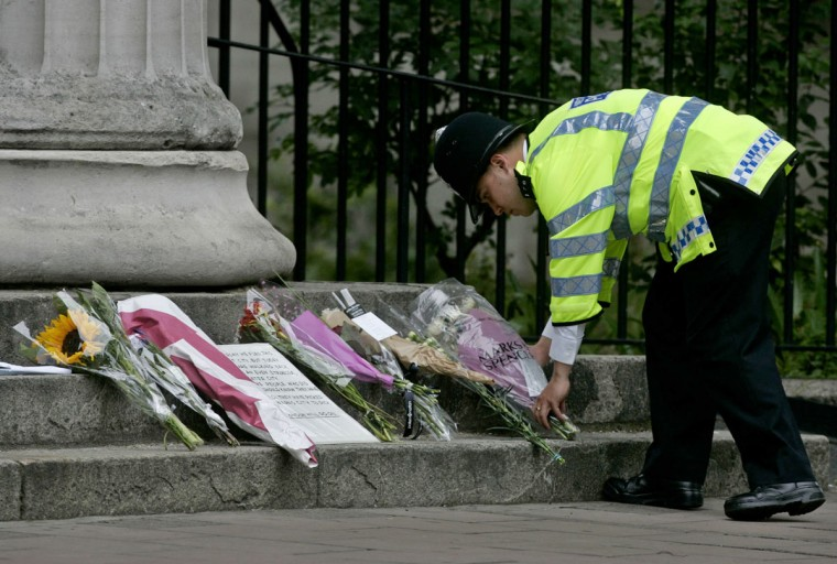 A British police officer lays flowers from a member of the public near the scene where an explosion on a bus took place in central London on July 8, 2005. Commuters in London reluctantly descended into the Underground on Friday morning, attempting to return to routine in the aftermath of four rush-hour blasts that killed at least 50 people. (AP Photo/Matt Dunham)