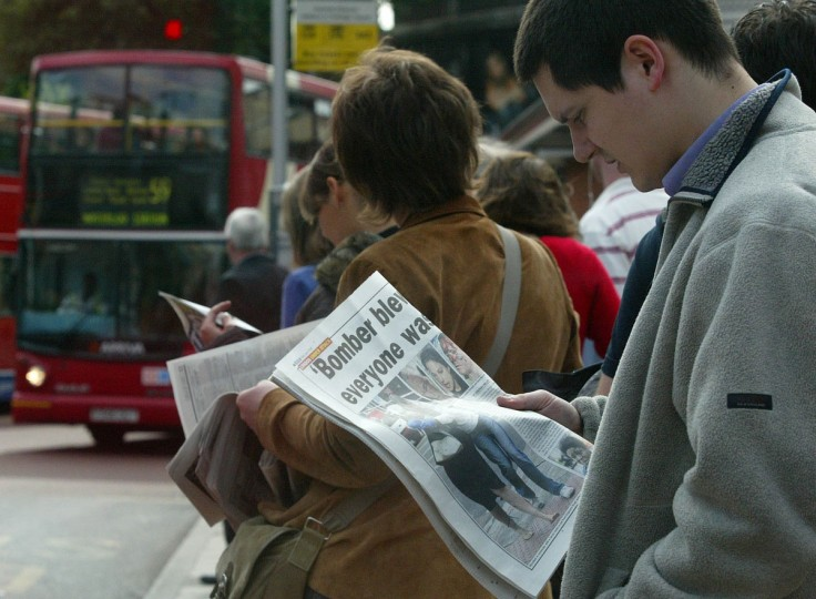 An early morning commuter reads newspaper reports while waiting for a bus at Waterloo Station, London on July 8, 2005. Commuters in London reluctantly descended into the Underground Friday morning, attempting to return to routine in the aftermath of four rush-hour blasts. (AP Photo / Sergio Dionisio)