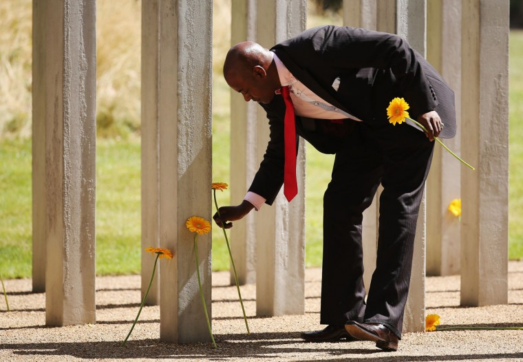 A man lays flowers at the 52 steel pillars memorial to the victims of the July 7, 2005 London bombings in Hyde Park on July 7, 2015 in London, England. It is the 10th anniversary of the 7/7 London bombings. (Photo by Dan Kitwood/Getty Images)