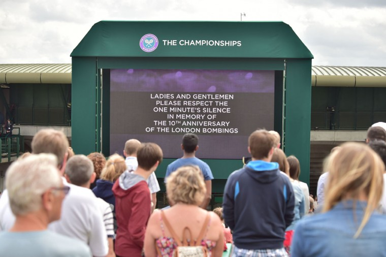 Spectators on Murray Mound (Henman Hill) stand to observe a minute's silence in memory of the 52 people who were killed in the 2005 London 7/7 suicide bombings on Day Eight of the 2015 Wimbledon Championships at The All England Tennis Club in Wimbledon, southwest London, on July 7, 2015. (LEON NEAL/AFP/Getty Images)