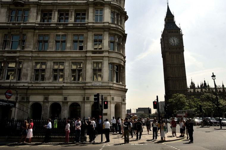 People wait for the alert to finish to go about their normal lives as British police officers block Whitehall, close to Prime Minister Tony Blair's official residence at 10 Downing Street, in central London, after a suspicious object was spotted, Wednesday July 13, 2005. St. Stephen's tower is seen on the right. New evidence suggests four suicide bombers, including at least three Britons of Pakistani descent, carried out the terror attacks in London, officials said. Surveillance cameras captured the men as they arrived in the capital 20 minutes before the explosions began. (AP Photo/Lefteris Pitarakis)