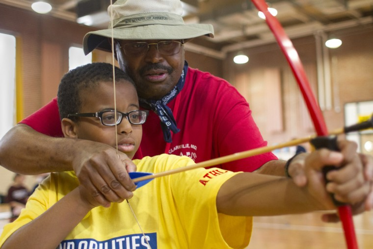 Clarksville Scout leader Chris Parrish Sr. teaches Denez Johnson, 12, how to use and bow and arrow during an archery shooting activity at Camp Abilities, hosted by the Maryland School for the Blind.  (Tom Brenner/ Baltimore Sun)