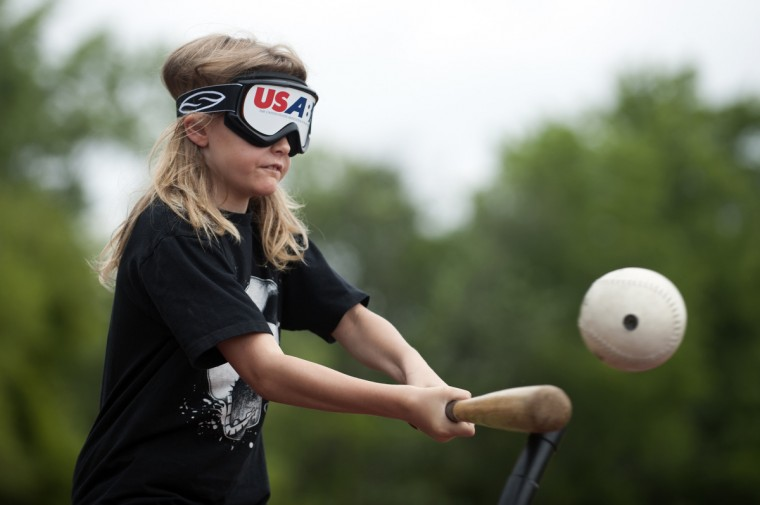 Robert Panasuk, 9, hits the baseball during a game of beep baseball at Camp Abilities, hosted at the Maryland School for the Blind.  Beep baseball is modified by putting speakers into the ball and bases that alert players during game play.  (Tom Brenner/ Baltimore Sun)