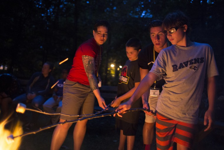 From left to right: Instructor Nicole Kirk, Jonathan Panasuk, 10, instructor Joey Mescall, and Aidan Hajek-Ellerman, 11, roast marsh mellows over a fire pit at Camp Abilities hosted by the Maryland School for the Blind.  (Tom Brenner/ Baltimore Sun)