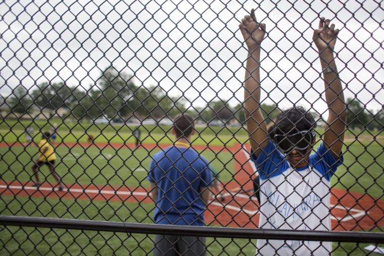 Shawn Abraham hangs onto the fence while waiting to bat during a game of beep baseball at Camp Abilities, hosted at the Maryland School for the Blind. (Tom Brenner/ Baltimore Sun)