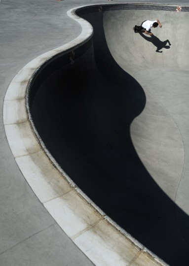 Zachary Lyon of Baltimore skates out of the shadows of the bowl at the Skatepark of Baltimore. (Lloyd Fox/Baltimore Sun)