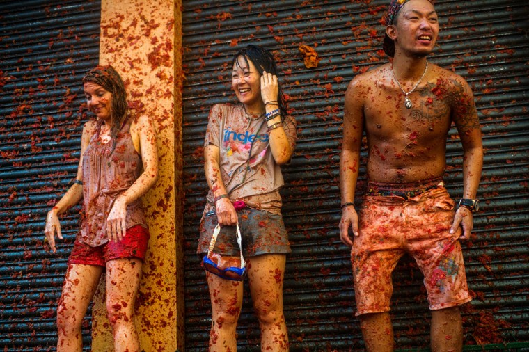 Revelers enjoy the atmosphere in tomato pulp while participating the annual Tomatina festival on August 26, 2015 in Bunol, Spain. An estimated 22,000 people threw 150 tons of ripe tomatoes in the world's biggest tomato fight held annually in this Spanish Mediterranean town. (Photo by David Ramos/Getty Images)
