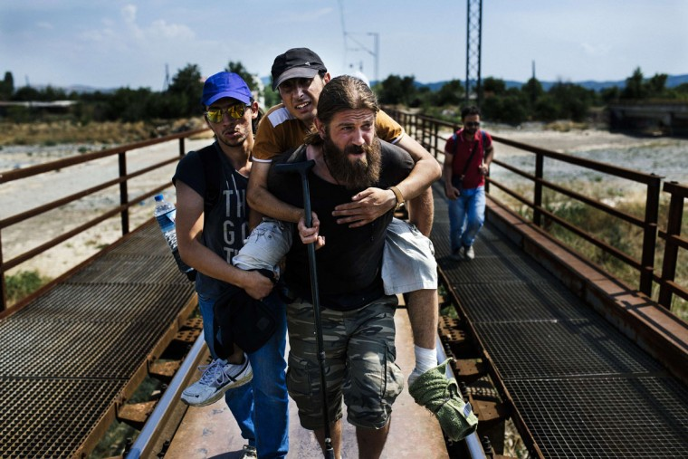 Syrian migrants carry their injured friend as they walk on railway tracks towards the town of Gevgelija on the Macedonian-Greek border on August 5, 2015. Many migrants try to cross Macedonia and Serbia to enter the European Union via Hungary, a country that will finish building its anti-migrant fence on its southern border with Serbia by August 31, ahead of a previous November deadline. (AFP Photo/Dimitar Dilkoff)