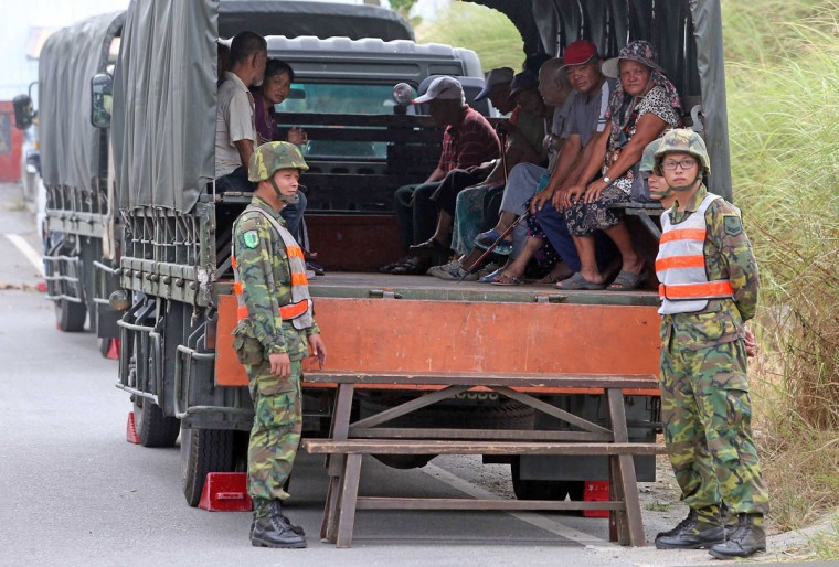 Military soldiers stand guard outside of the trucks while evacuating local residents from Gian village in Hualien as Typhoon Soudelor approaches eastern Taiwan on August 7, 2015. An eight-year-old girl died after being swept out to sea off Taiwan as Typhoon Soudelor bore down on the island, forcing thousands to flee and troops to be placed on standby, officials said. (AFP Photo/Allen Chen)