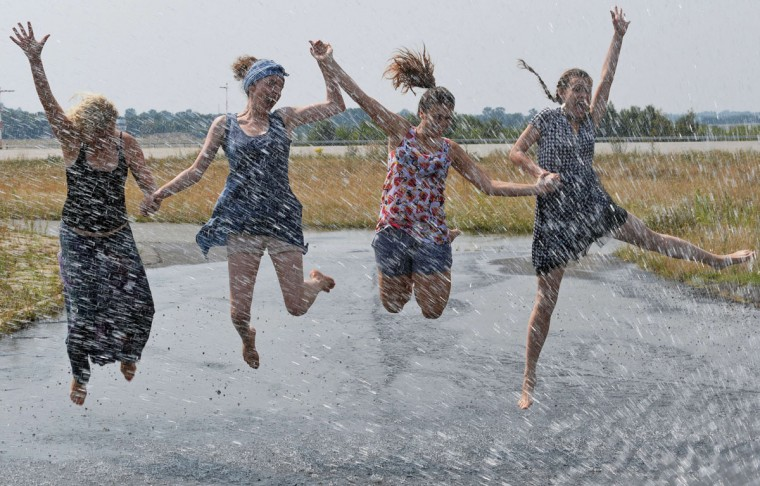 Girls who help to organize the first TPG Deafblind Race cool off in a hydrant's water squirt on August 9, 2015, at the airport in Lodz, central Poland, as temperatures reached 35 degrees Celsius. (AFP Photo/Janek Skarzynski)