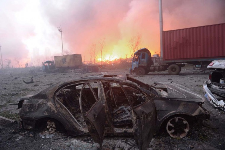 This photo taken on August 13, 2015 shows a destroyed car as a fire continues to burn after a series of explosions at a chemical warehouse hit the city of Tianjin, in northern China. A Chinese military team of nuclear and chemical experts began work on August 14 at the site of two massive explosions in the city of Tianjin, state media said, as pressure grows for authorities to explain the cause of blasts that left 50 dead.      AFP/Getty Images