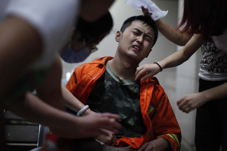This photo taken on August 13, 2015 shows people taking care of an injured rescuer (C) in a hospital in Tianjin.  Massive explosions at a chemical storage facility in one of China's biggest cities killed at least 50 people and injured 700. They also raised fears about toxic chemicals poisoning the air.     AFP/Getty Images