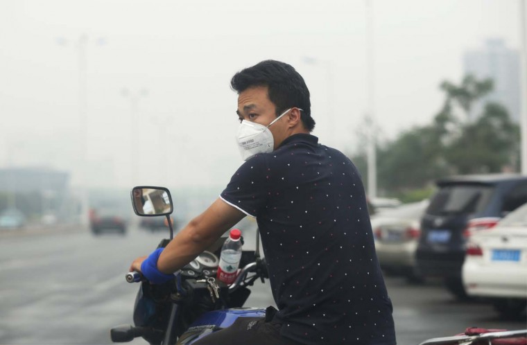 A resident wears a mask as he rides his scooter on a street in Tianjin on August 14, 2015.  A Chinese military team of nuclear and chemical experts began work on August 14 at the site of two massive explosions in the city of Tianjin, state media said, as pressure grows for authorities to explain the cause of blasts that left 50 dead. AFP/Getty Images