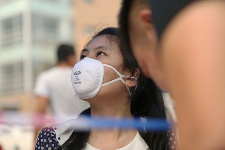 A girl (C) wears a mask in a temporary shelter after the explosions in Tianjin on August 14, 2015. A Chinese military team of nuclear and chemical experts began work on August 14 at the site of two massive explosions in the city of Tianjin, state media said, as pressure grows for authorities to explain the cause of blasts that left 50 dead. AFP/Getty Images