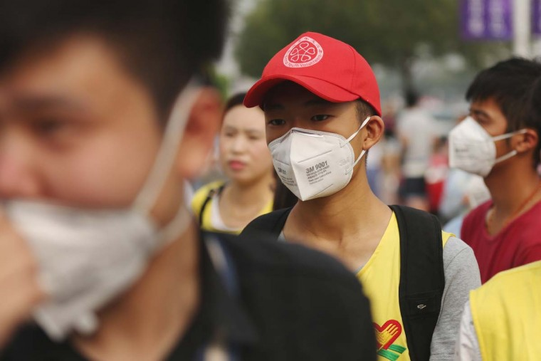 A volunteer (C) wears a mask in a temporary shelter after the explosions in Tianjin on August 14, 2015. A Chinese military team of nuclear and chemical experts began work on August 14 at the site of two massive explosions in the city of Tianjin, state media said, as pressure grows for authorities to explain the cause of blasts that left 50 dead. AFP/Getty Images
