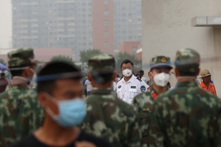 Volunteers and paramilitary soldiers wearing masks stand on patrol outside a temporary shelter after the explosions in Tianjin on August 14, 2015. A Chinese military team of nuclear and chemical experts began work on August 14 at the site of two massive explosions in the city of Tianjin, state media said, as pressure grows for authorities to explain the cause of blasts that left 50 dead. AFP/Getty Images