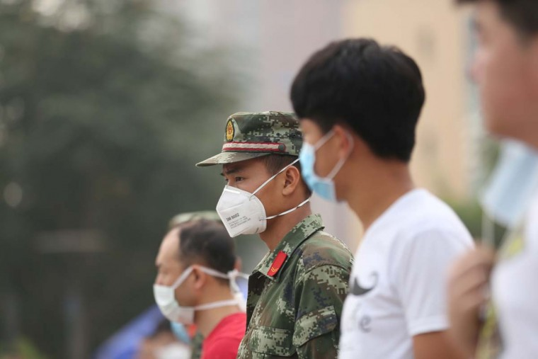 Volunteers and paramilitary soldiers wearing masks stand on patrol outside a temporary shelter after the explosions in Tianjin on August 14, 2015. A Chinese military team of nuclear and chemical experts began work on August 14 at the site of two massive explosions in the city of Tianjin, state media said, as pressure grows for authorities to explain the cause of blasts that left 50 dead. CHINA OUT     AFP PHOTOSTR/AFP/Getty Images ORG XMIT:
