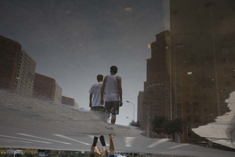 Water reflects the shadows of two man walking in a residential area close to the site of the explosions in Tianjin on August 14, 2015. A Chinese military team of nuclear and chemical experts began work on August 14 at the site of two massive explosions in the city of Tianjin, state media said, as pressure grows for authorities to explain the cause of blasts that left 50 dead. AFP/Getty Images