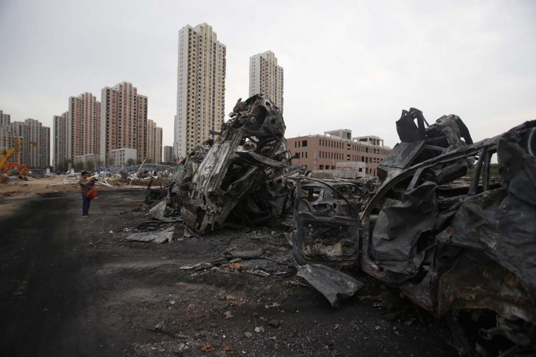 A man takes a photo of damaged cars at the site of the explosions in Tianjin on August 14, 2015.  Enormous explosions in a major Chinese port city killed at least 44 people and injured more than 500, state media reported on August 13, leaving a devastated industrial landscape of incinerated cars, toppled shipping containers and burnt-out buildings. CHINA OUT AFP PHOTOSTR/AFP/Getty Images ORG XMIT: