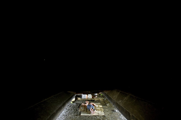 A homeless man sleeps under a flyover in Manila on Tuesday. Roughly one quarter of the nation's 100 million people live in poverty, which is defined as surviving on about one U.S. dollar a day, according to government data. (NOEL CELISNOEL CELIS/AFP/Getty Images)