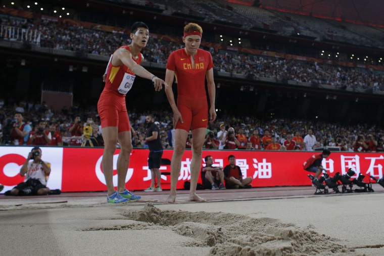 "China's Gao Xinlong (L) and China's Li Jinzhe inspect the mark in the final of the men's long jump athletics event at the 2015 IAAF World Championships at the ""Bird's Nest"" National Stadium in Beijing on August 25, 2015.  (ADRIAN DENNIS/AFP/Getty Images)"