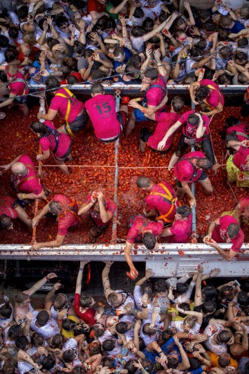 "Revelers throw tomato pulp in the annual ""tomatina"" festivities in the village of Bunol, near Valencia on August 26, 2015. Some 22,000 revelers hurled 150 tons of squashed tomatoes at each other drenching the streets in red in a gigantic Spanish food fight marking the 70th annual ""Tomatina"" battle. (AFP Photo/Biel Alino)"
