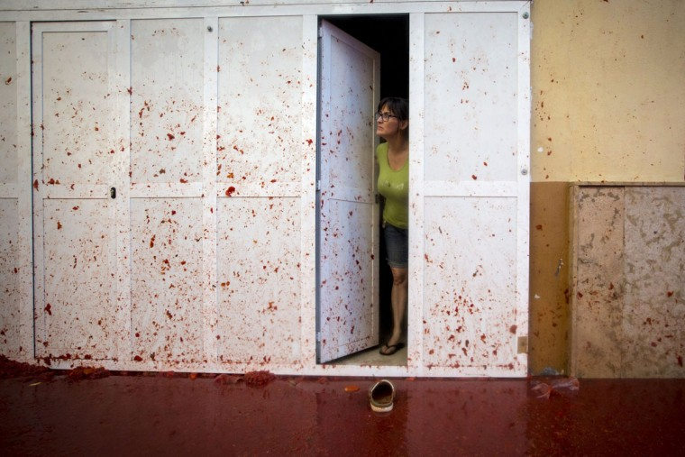 "A woman stands in a doorway covered in tomato pulp during the annual ""tomatina"" festivities in the village of Bunol, near Valencia on August 26, 2015. Some 22,000 revelers hurled 150 tons of squashed tomatoes at each other drenching the streets in red in a gigantic Spanish food fight marking the 70th annual ""Tomatina"" battle. (AFP Photo/Biel Alino)"