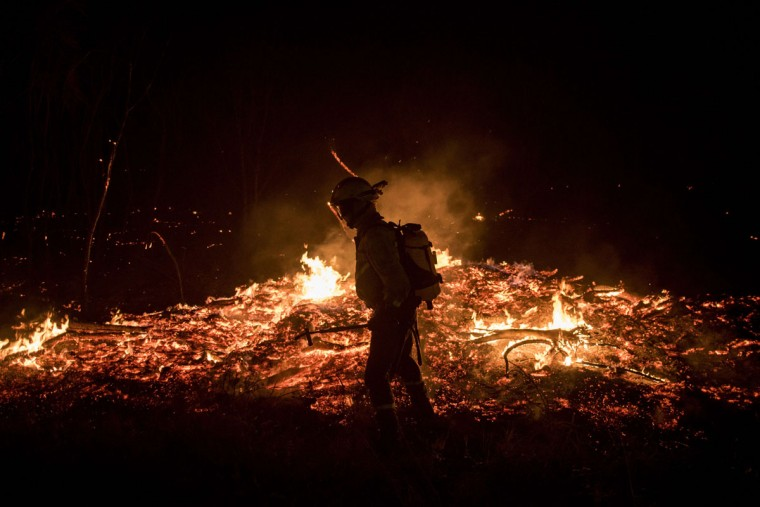 A firefighters tries to extinguish flames at the site of a wildfire in Cualedro, near Ourense on August 30, 2015. A fire broke out today around noon in the Cualedro town in Galicia, northwest Spain, affecting at least 1,000 hectares of forest, as seven fires continued to burn in Spain, three in Galicia, one in Cantabria, one in Castile and Leon, one in Catalonia and Extremadura. (AFP Photo/Pedro Armestre)