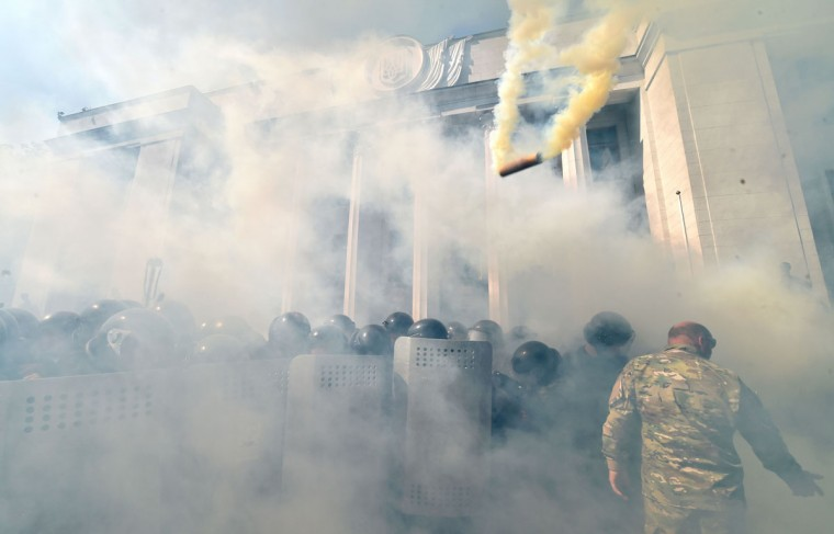 "Smoke rises from the parliament building in Kiev as activists of radical Ukrainian parties, including the Ukrainian nationalist party Svoboda (Freedom), clash with police officers on August 31, 2015. At least 20 were wounded in clashes outside parliament in Kiev after lawmakers gave initial approval to constitutional changes granting more autonomy to pro-Russian separatists in eastern Ukraine. A loud blast was heard outside parliament shortly after the bill was passed, an AFP journalist said. Ukrainian interior ministry advisor and top lawmaker Anton Gerashchenko wrote on Facebook that attackers threw a hand grenade at National Guard troops guarding the building in what he called an ""act of provocation."" (AFP Photo/Sergei Supinsky)"