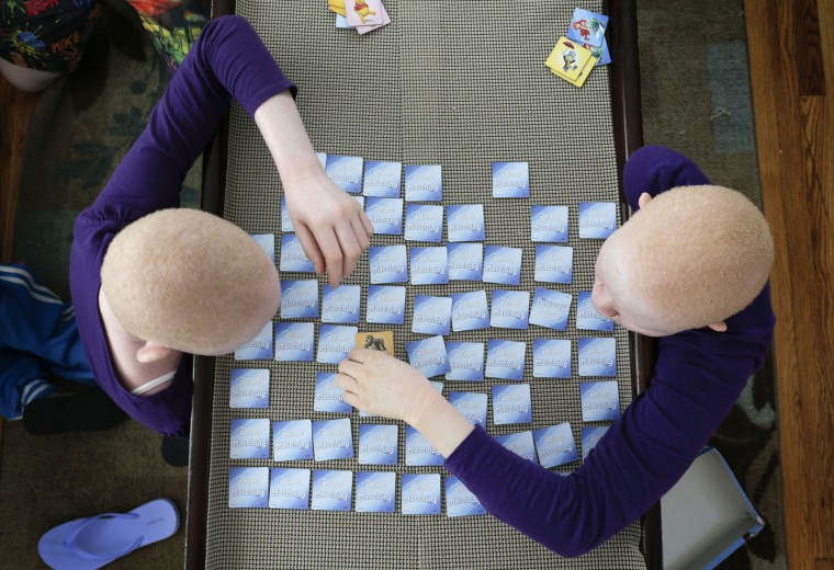 Pendo Noni, left, and Kabula Masanja play a memory card game in New York on Tuesday, July 28, 2015. One out of every 1,400 citizens in Tanzania has albinism. Pendo and Kabula were attacked and dismembered in the belief that their body parts will bring wealth. (AP Photo/Julie Jacobson)