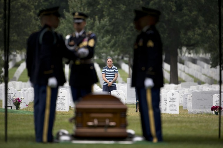 Army Sgt. 1st Class Krystle McGrath of Fort Bragg, N.C., stands in the distance at the grave of her friend Army Sgt. 1st Class Matthew I. Leggett, to acknowledged the burial service for World War II U.S. Army Air Forces Staff Sgt. Ward C. Swalwell, Jr., 21, of Chicago, at Arlington National Cemetery in Arlington, Va., Thursday, Aug. 20, 2015. McGrath was Leggett's grave who died Aug. 20, 2014, a year ago today, in Kabul, Afghanistan, of injuries received when he was engaged by the enemy. McGrath was with Leggett when he died. (AP Photo/Carolyn Kaster)
