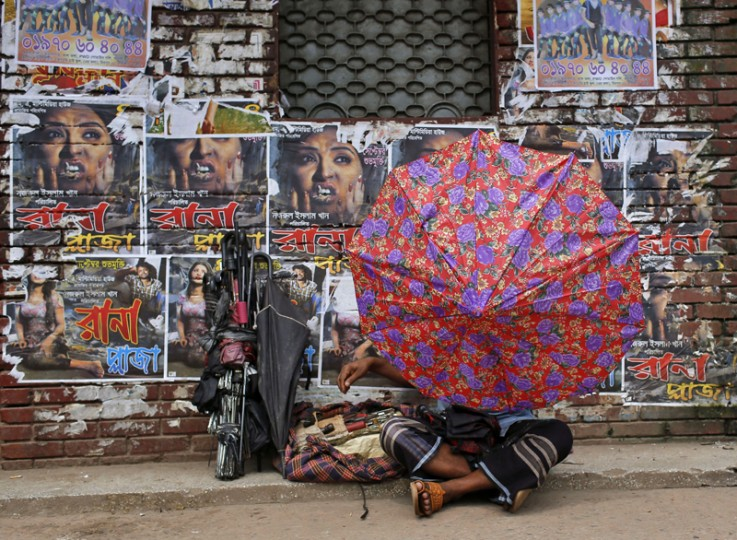 "A Bangladeshi man fixes an umbrella as he sits in front of the posters of a film ""Rana Plaza"" pasted on the wall of a movie theatre in Dhaka, Bangladesh, Tuesday. Bangladesh's High Court has imposed a six-month ban on the screening of the movie about a garment worker who was rescued from the rubble 17 days after a five-story factory complex collapsed more than two years ago, killing more than 1,000 people. (A.M. Ahad/AP)"