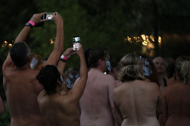 A man and a woman take photos of competitors of a 'Tiger Streak' at London Zoo where people run around a 300m course in the zoo in the nude to raise money for Tiger conservation projects, in London, Thursday, Aug. 13, 2015. (AP Photo/Alastair Grant)