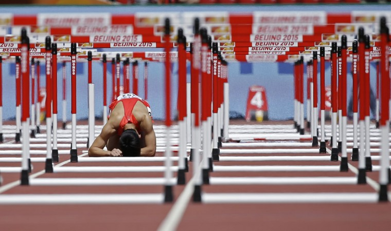 China's Zhang Honglin reacts after getting injured in a menís 110m hurdles round one heat at the World Athletics Championships at the Bird's Nest stadium in Beijing, Wednesday, Aug. 26, 2015. (AP Photo/David J. Phillip)