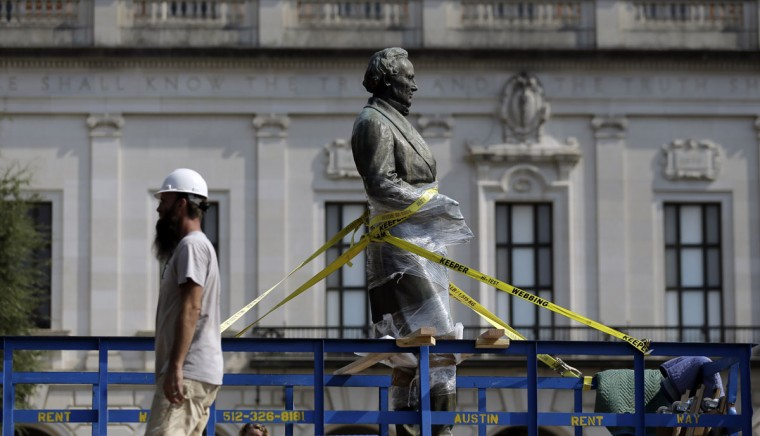 A statue of Confederate President Jefferson Davis is moved from its location in front of the school's main tower the University of Texas campus, Sunday, Aug. 30, 2015, in Austin, Texas. The Davis statue, which has been targeted by vandals and had come under increasing criticism, will be moved and placed in the school's Dolph Briscoe Center for American History as part of an educational display. (AP Photo/Eric Gay)