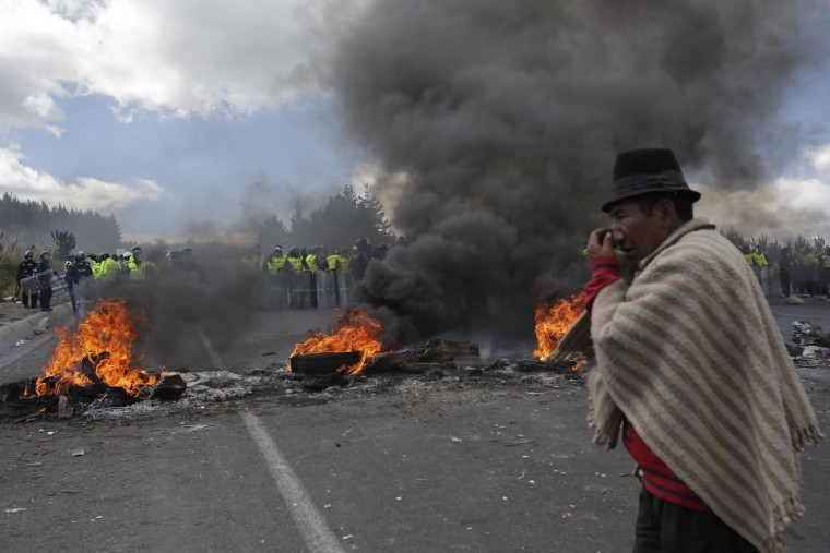 An indigenous protester from the highlands stands at a burning roadblock along the Panamerican Highway during a general strike in the Chasqui area of Ecuador, Thursday, Aug. 13, 2015. A strike by a broad coalition upset with President Rafael Correa virtually paralyzed the capital, provincial cities and stretches of the Panamerican highway. The protesters are indigenous activists, unionists, environmentalists and members of the traditional political opposition. (AP Photo/Dolores Ochoa)
