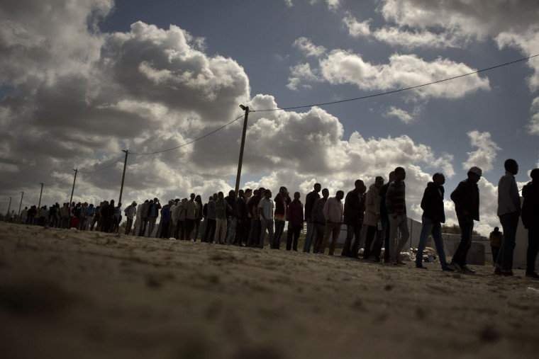 Migrants line up as the wait for a food ration distributed by the Banque Alimentaire of Calais at a camp in northern France, Tuesday, Aug. 4, 2015. The European Union is offering funds and aid to help France cope with growing numbers of migrants near the northern city of Calais. It comes as thousands of migrants have been scaling fences near the Channel Tunnel linking the two countries and boarding freight trains or trucks destined for Britain. (AP Photo/Emilio Morenatti)