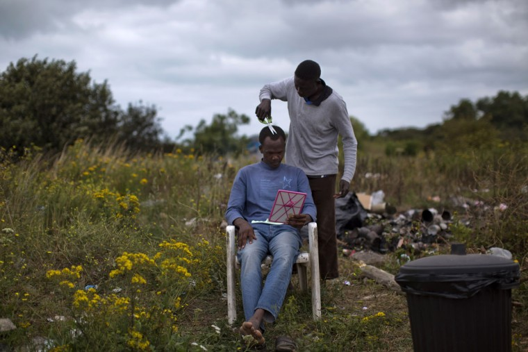 A Sudanese migrant gets a hair cut at a camp set near Calais, northern France, Thursday, Aug. 6, 2015. Thousands of migrants have been scaling fences near the Channel Tunnel linking the two countries and boarding freight trains or trucks destined for Britain. (AP Photo/Emilio Morenatti)