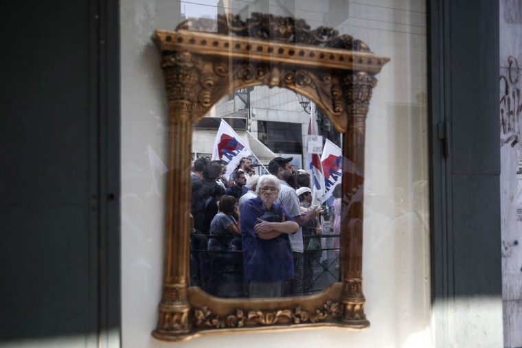 Supporters of the Communist-affiliated PAME labor union are reflected on a mirror as they take part in an anti-austerity rally outside the Labor Ministry in Athens, Greece, on Wednesday, Aug. 5, 2015. Greece's economy is reeling from the impact of limits on money withdrawals and transfers that the government imposed on June 29 to avoid a collapse of the banking sector. Uncertainty over Greece's negotiations for a new bailout and over the stability of the government have heightened concerns. (AP Photo/Yorgos Karahalis)