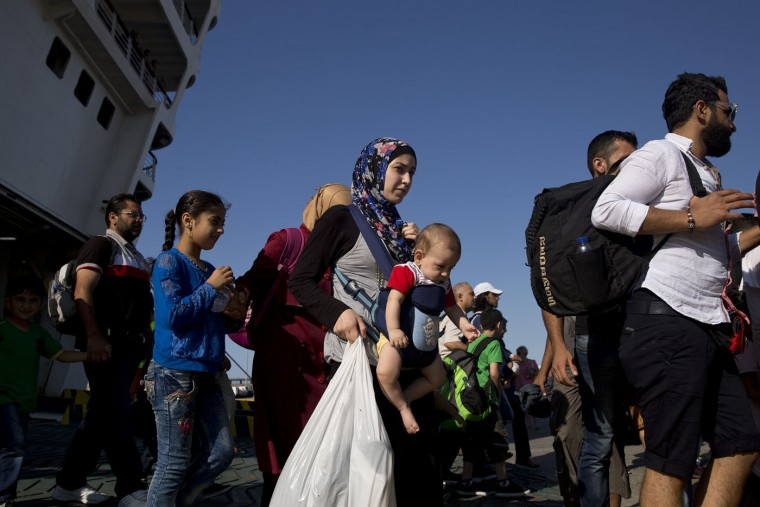 Syrian Refugees come out from a ferry carrying about 2,500 migrants from Greek islands to Greece's main port of Piraeus near Athens, on Thursday, Aug. 20, 2015. Greece has been overwhelmed this year by record numbers of migrants arriving on its eastern Aegean islands, with more than 160,000 arriving since January. (AP Photo/Petros Giannakouris)