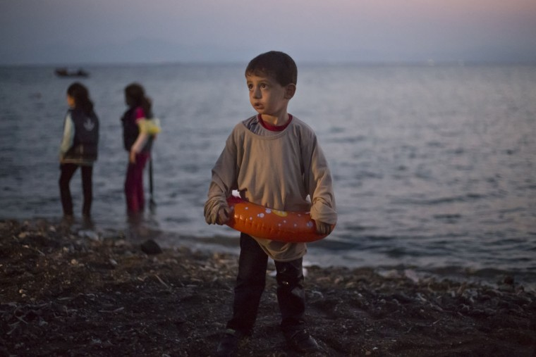 A Syrian migrant boy still wearing a swimming ring stands on the beach upon his arrival with other migrants by a dinghy at the southeastern Greek island of Kos, Greece, early Thursday, Aug. 20, 2015. Greece this year has been overwhelmed by record numbers of migrants arriving on its eastern Aegean islands, with more than 160,000 landing so far.(AP Photo/Alexander Zemlianichenko)