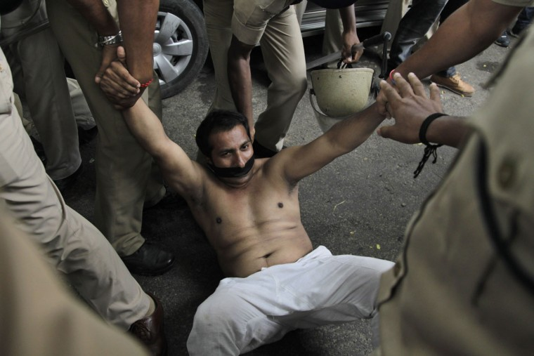 Indian policemen try to stop a bare chest protester of India's opposition Congress party's youth wing during a protest in New Delhi, India, Thursday, Aug. 6, 2015. The protesters demonstrated against the decision of Lok Sabha, or the lower house speaker, Sumitra Mahajan of the ruling Bharatiya Janata Party (BJP), who suspended 25 Congress party members from the Lok Sabha. The opposition also continued to demand the resignation of the two leaders of BJP for allegedly helping a former Indian cricket official facing investigation for financial irregularities. (AP Photo/Rishabh R. Jain)