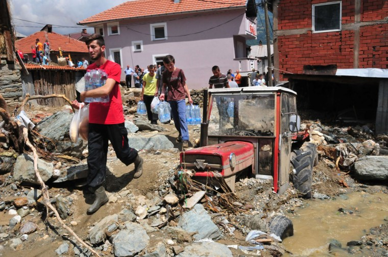 People carry food and water past a tractor stuck in mud, stones and debris that were piled in a flood in the mountain village of Sipkovica, just above the town of Tetovo, in northwestern Macedonia, on Tuesday, Aug. 4, 2015. A small number of people including children have died in floods that erupted after an hour of heavy torrential rains and strong winds that hit Tetovo and northwestern region of Macedonia late on Monday.