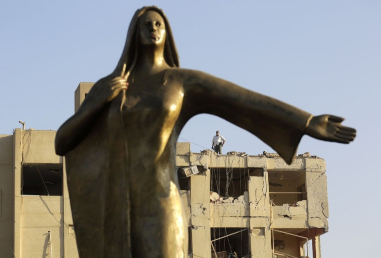 An Egyptian plainclothes policeman stands on the top of the damaged national security building after a bomb exploded early Thursday, Aug. 20, 2015, in the Shubra el-Kheima neighborhood of Cairo, injuring several people, Egyptian security officials said. The statue represents an Egyptian farmer. (AP Photo/Amr Nabil)